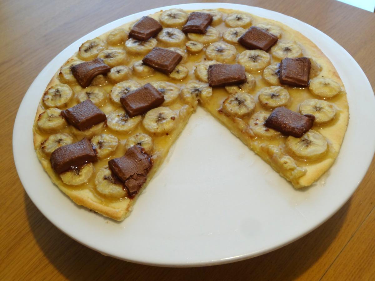 Tarte banane et chocolat au lait avec une part découpé